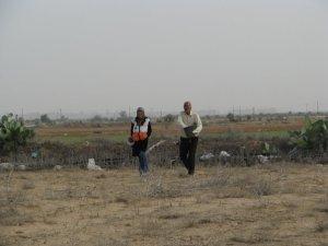 Farmer sows seeds while ISM volunteer walks alongside him.