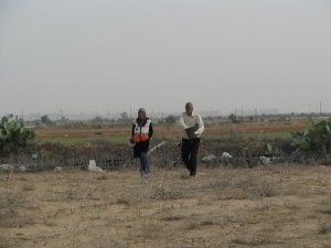 Farmer sows seeds while ISM volunteer walks alongside him.