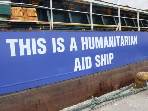 Signs on the side of the large passenger ship read 'This is a humanitarian ship', in English, Arabic and Hebrew