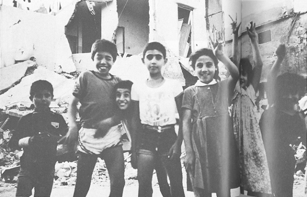 Children standing in destroyed Sabra and Shatila camps raise the victory salute, Beirut, September 1982